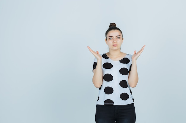 Young lady showing helpless gesture in t-shirt, jeans and looking puzzled. front view.