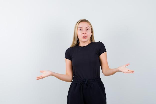 Giovane signora che mostra gesto impotente in maglietta, pantaloni e che sembra eccitata. vista frontale.