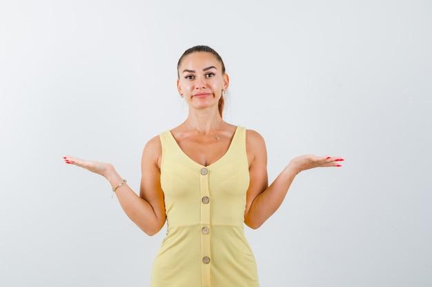 Giovane signora che mostra gesto impotente in vestito giallo e che sembra confusa. vista frontale.