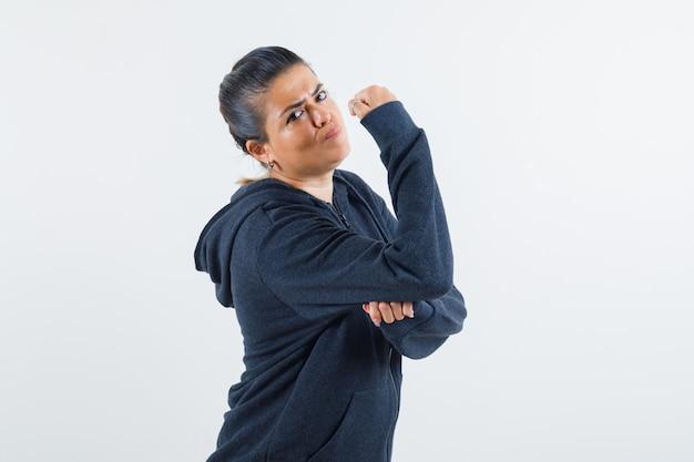 ジャケットを着て腕の筋肉を見せ、厳格に見える若い女性。正面図。