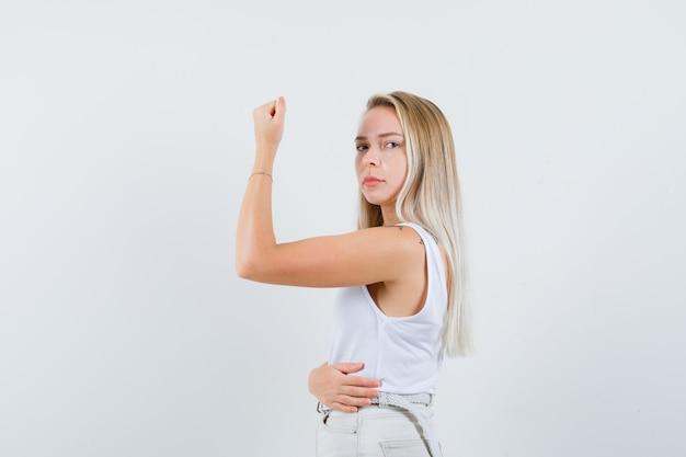 白いブラウスで腕の筋肉を見せて、厳格に見える若い女性 無料写真