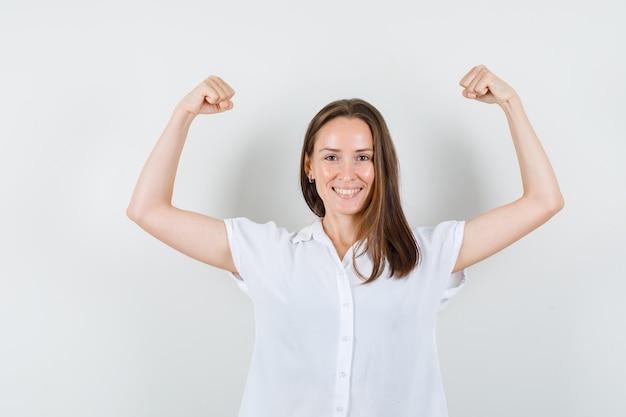 Giovane signora che mostra i suoi muscoli del braccio in camicetta bianca e sembra in buona salute