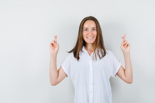 Молодая дама показывает скрещенные пальцы, улыбаясь в белой блузке и выглядит весело.