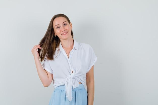 ブラウスとスカートに笑みを浮かべて、かわいく見える間、彼女の髪を見せている若い女性