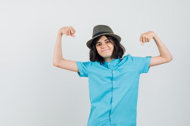 Giovane donna che mostra il suo potere in camicia blu, cappello e sguardo energico.
