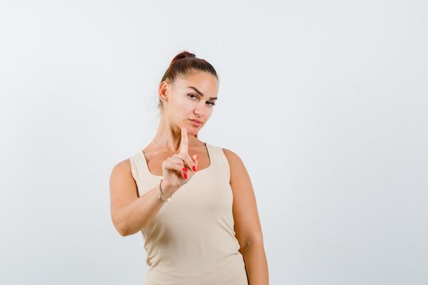 Молодая дама показывает удержание минутного жеста в майке и выглядит уверенно. передний план.