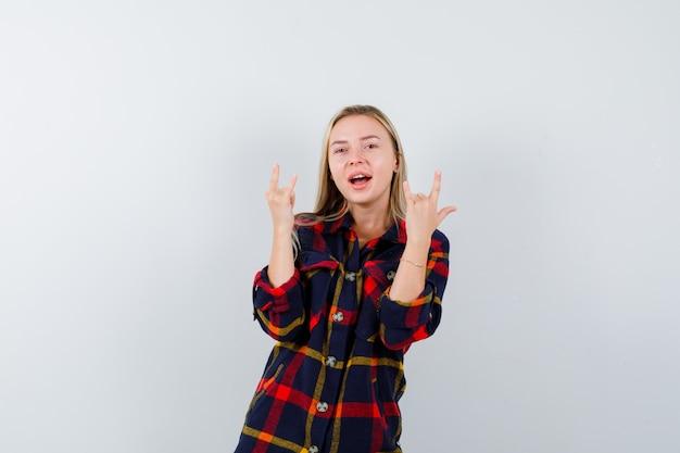 Юная леди показывает жест в клетчатой рубашке и выглядит энергичным, я люблю тебя, вид спереди.