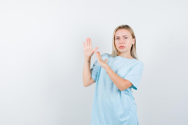 Молодая дама показывает жест каратэ отбивные в изолированной футболке