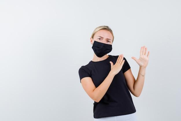 Девушка в футболке, брюках, медицинской маске демонстрирует отбивные для карате и выглядит уверенно