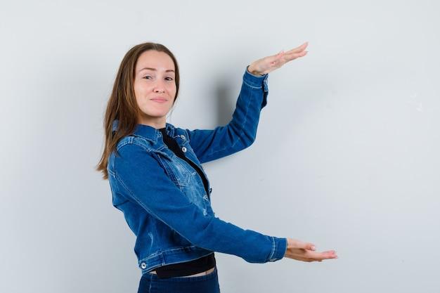 Giovane donna che mostra un gesto di grandi dimensioni in camicetta, giacca e sembra sicura. vista frontale.