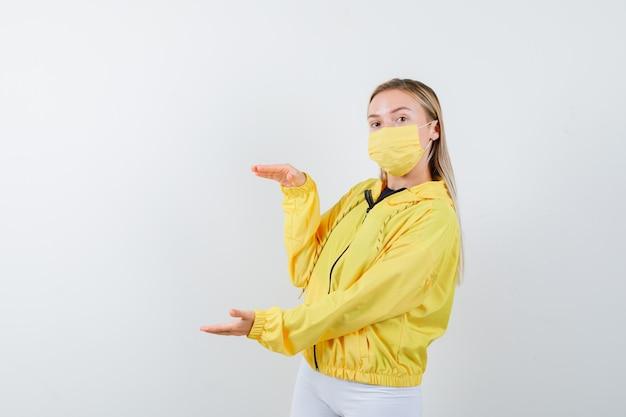 ジャケット、パンツ、マスクで大きなサイズのサインを示し、自信を持って、正面図を見て若い女性。