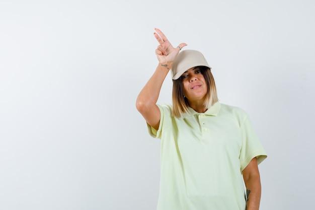 Молодая леди показывает жест проигравшего в футболке, кепке и задумчиво, вид спереди.