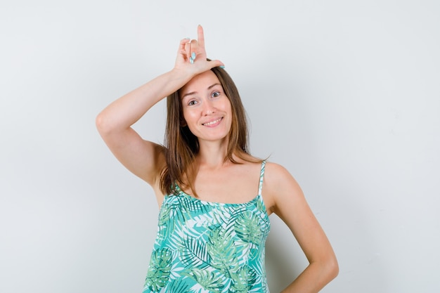 Young lady showing loser sign on forehead and looking cheery , front view.