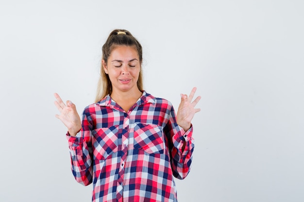 Giovane donna che mostra gesto di meditazione in camicia a quadri e guardando rilassato, vista frontale.