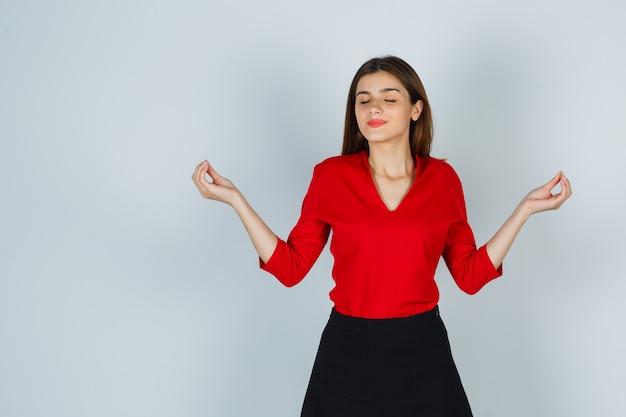 赤いブラウス、スカートで瞑想のジェスチャーを示し、平和に見える若い女性