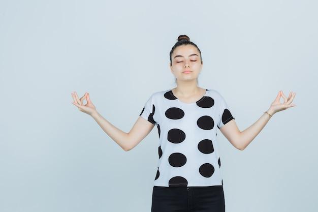 Tシャツ、ジーンズで瞑想のジェスチャーを示し、希望に満ちた正面図を探している若い女性。