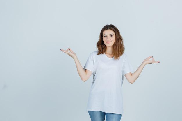 Giovane signora che mostra il gesto di meditazione in maglietta, jeans e che sembra pacifica, vista frontale.