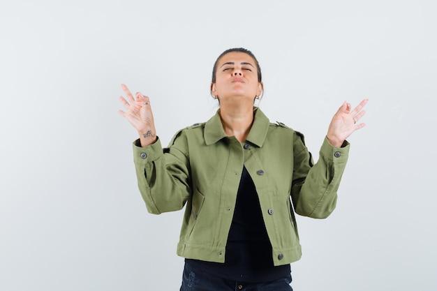 Giovane signora che mostra gesto di meditazione in maglietta