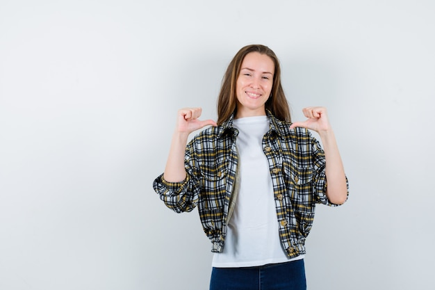 Tシャツ、ジャケット、ジーンズで中親指を示し、幸せそうに見える若い女性、正面図。