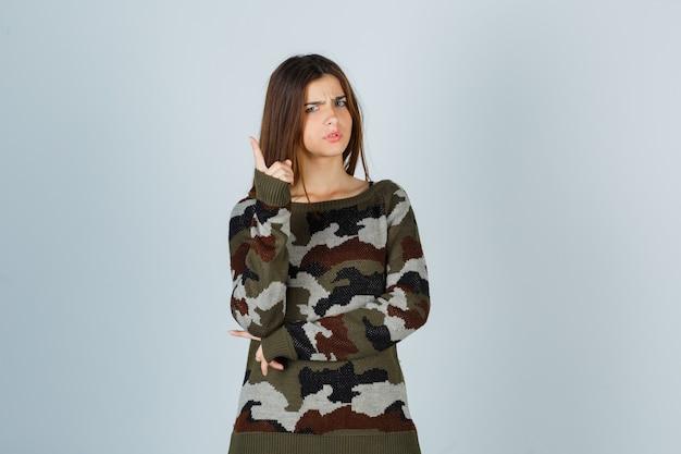 Giovane donna che mostra un gesto minuto in maglione e sembra seria