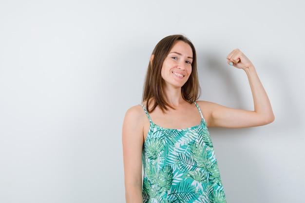 Giovane donna che mostra i muscoli del braccio e sembra allegra. vista frontale.