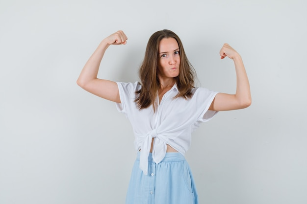 Young lady showing muscles of arms in blouse and skirt and looking confident