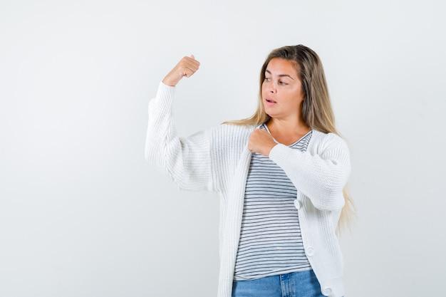 T- 셔츠, 재킷에 팔의 근육을 보여주는 자신감을 찾고 젊은 아가씨. 전면보기.