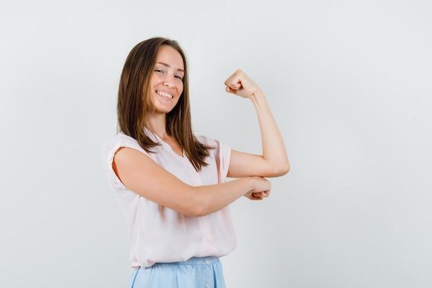 Молодая дама показывает мышцы рук в футболке, юбке и выглядит уверенно. передний план.