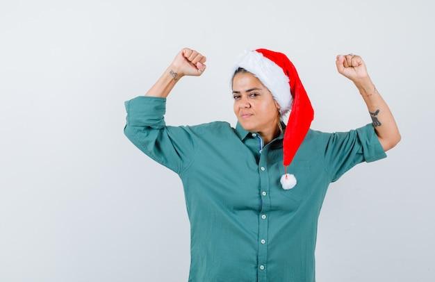 クリスマスの帽子、シャツ、自信を持って、正面図で腕の筋肉を示す若い女性。