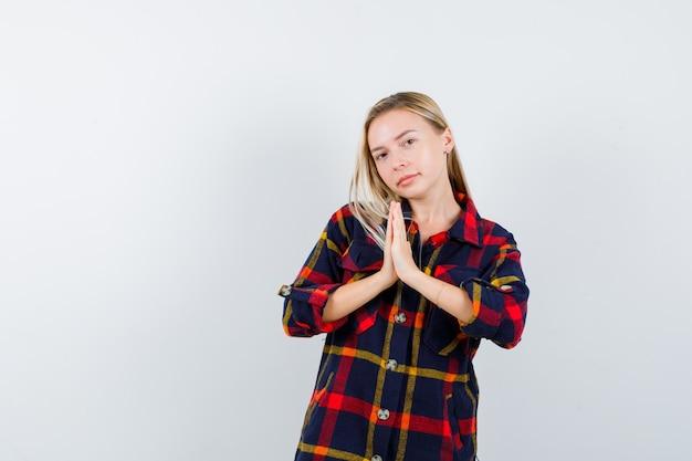 チェックのシャツでナマステのジェスチャーを示し、希望に満ちた若い女性。正面図。