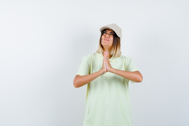 T- 셔츠, 모자 및 평화로운 찾고 나마스테 제스처를 보여주는 젊은 아가씨. 전면보기.