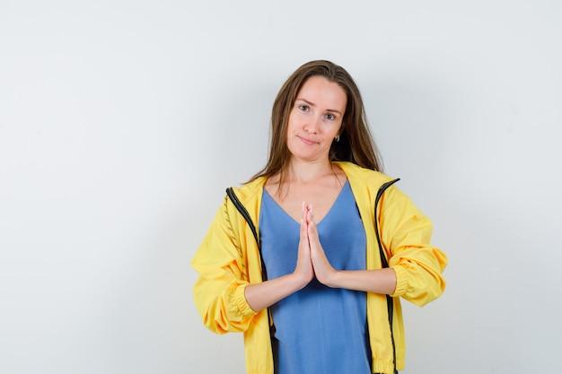 Tシャツ、ジャケットでナマステのジェスチャーを示し、希望に満ちた正面図を探している若い女性。