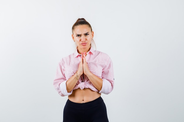 Giovane signora che mostra il gesto di namaste in camicia, pantaloni e sguardo pieno di speranza