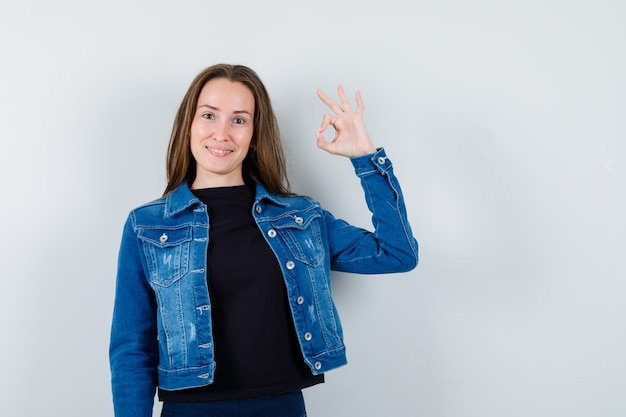 Young lady showing ok gesture in blouse, jacket and looking confident. front view.
