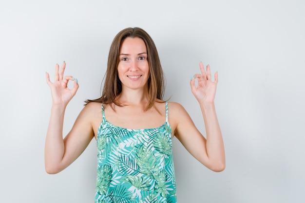 Giovane donna che mostra gesto ok in camicetta e sembra felice, vista frontale.
