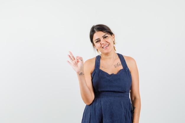 Giovane donna che mostra gesto ok in abito e sembra allegra