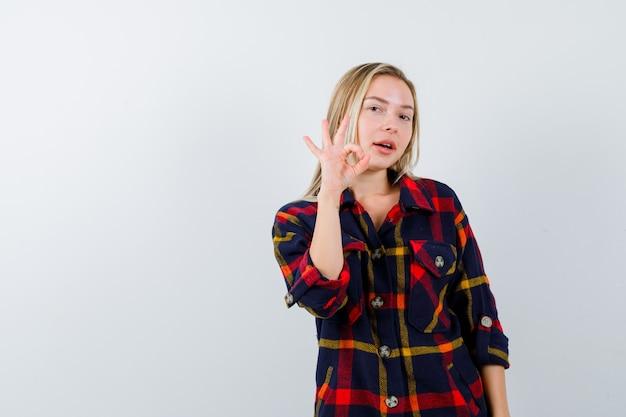 チェックのシャツで大丈夫なジェスチャーを示し、自信を持って見える若い女性。正面図。