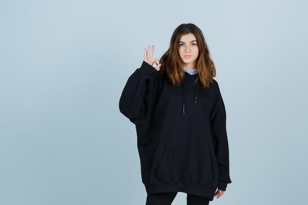 Юная леди показывает жест в негабаритной толстовке с капюшоном, штанах и выглядит уверенно, вид спереди.