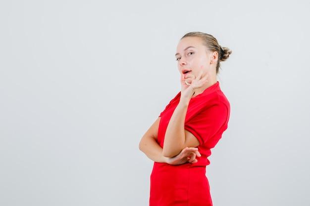 赤いtシャツでokジェスチャーを示し、自信を持って見える若い女性