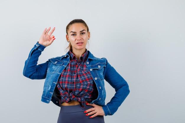 Молодая леди показывает нормально жест в рубашке, куртке и выглядит уверенно, вид спереди.