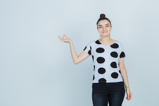 T- 셔츠, 청바지에 확인 제스처를 표시 하 고 즐거운 찾고 젊은 아가씨. 전면보기.