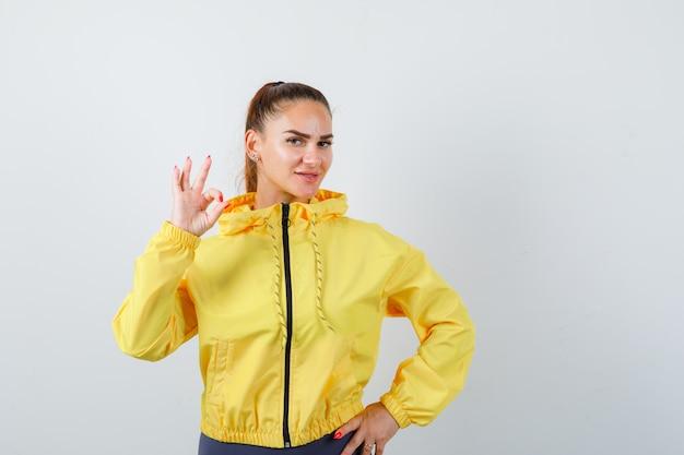 Молодая леди показывает нормально жест в желтой куртке и выглядит довольным, вид спереди.