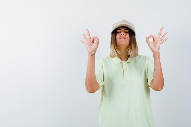 Tシャツ、キャップで目に大丈夫なジェスチャーを示し、自信を持って見える若い女性。正面図。