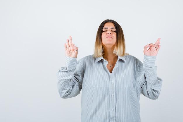 Giovane donna che mostra gesto ok in camicia oversize e sembra pacifica. vista frontale.