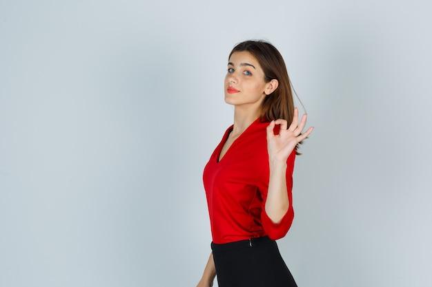 Giovane signora che mostra gesto giusto in camicetta rossa, gonna e sembra sicura