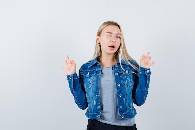Tシャツ、デニムジャケット、スカートでまばたきしながら大丈夫なジェスチャーを示し、うれしそうに見える若い女性