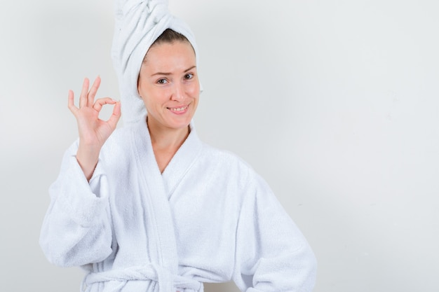 Young lady showing ok gesture in white bathrobe, towel and looking happy. front view.
