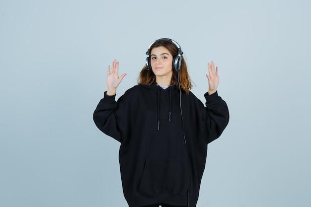 Юная леди показывает ладони в огромной толстовке с капюшоном, брюках и очаровательно выглядит, вид спереди.