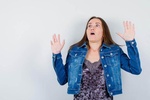 ブラウス、デニムジャケットで降伏のジェスチャーで手のひらを示し、怖がって見える若い女性。正面図。