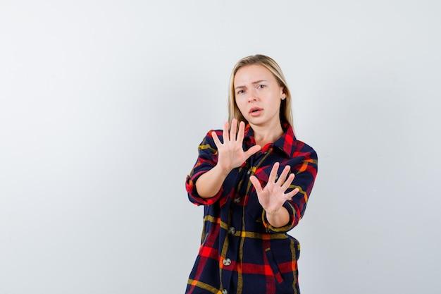 Молодая леди показывает ладони в жесте капитуляции в клетчатой рубашке и выглядит испуганной, вид спереди.